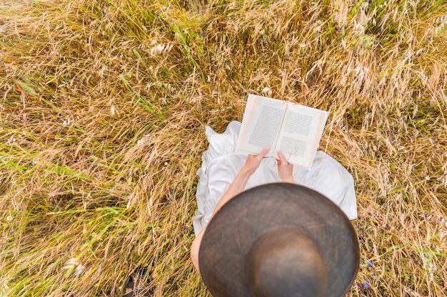 本を読んで春を祝う黄色い小麦の牧草地に座っている白い自由奔放に生きるドレスを着た若い認識できない女性の上からの眺め。物語への情熱を持って自然の中で時間を過ごすのんきな女の子