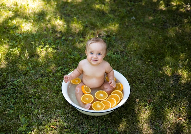The view from the top. a small beautiful girl is sitting in a tub of oranges on the green grass and looks at the camera