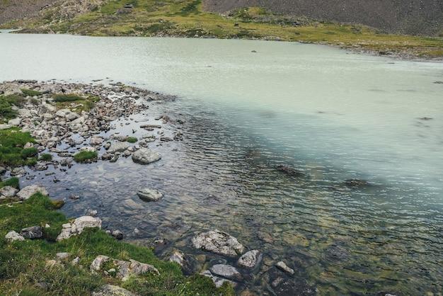 透明な水で上からターコイズブルーの山の湖までの眺め。石と草に囲まれた氷河湖のターコイズブルーの水面のある雰囲気のある山の風景。上から高原の湖までの眺め。