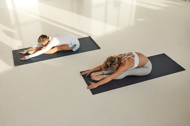 View from top of two young people man and woman with muscular flexible bodies wearing sports clothes practicing yoga together, sitting on mats, doing paschimottasana. sports, health and flexibility
