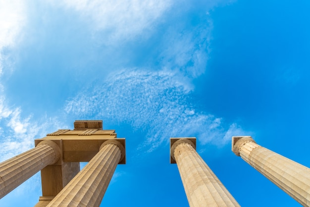 View from below towards a blue sky of an ancient greek pillars of the acropolis of lindos.
