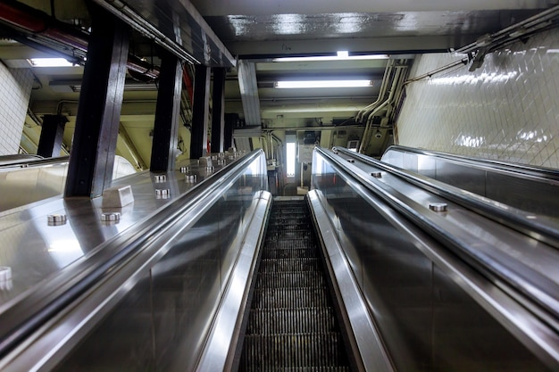 View from above of two-way escalators with staircase at subway