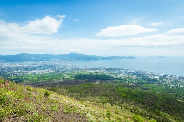 이탈리아의 베수비오 화산에서 하늘을 배경으로 바다와 도시의 해안을 바라 봅니다.
