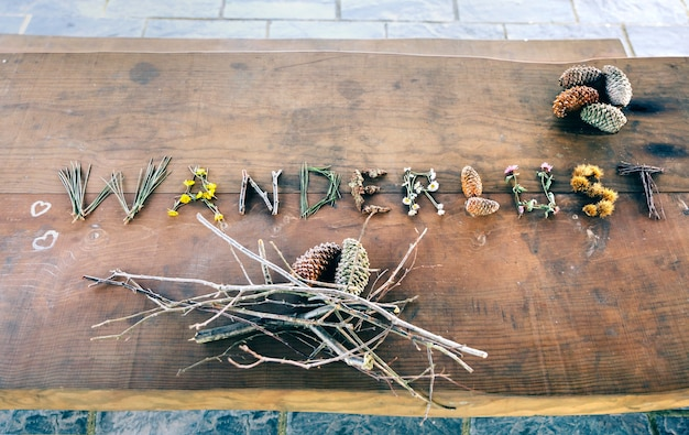 View from above of wanderlust word made with natural objects over wooden table