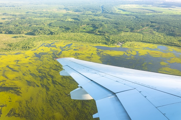 View from window of airplane to forests, fields, lakes, swamps