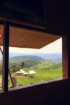 Вид из окна на ландшафтном рисовом поле с горами и небом.