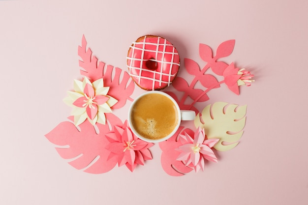 View from above with cup of coffee, donut and modern origami handcraft paper flowers copy space