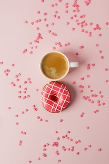 View from above with cup of coffee and pink donut, heart shape confetti copy space. woman day