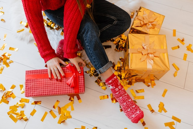 View from above on woman in red socks sitting at home at christmas on golden confetti unpacking peresents and gift boxes
