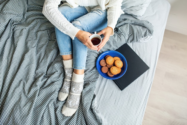 View from above of woman sitting on bed in morning, drinking coffee in cup, eating cookies, breakfast