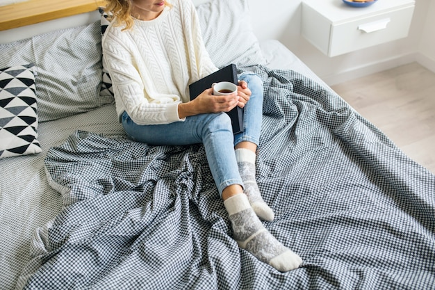 View from above of woman sitting on bed in morning, drinking coffee in cup, holding book, wearing jeans