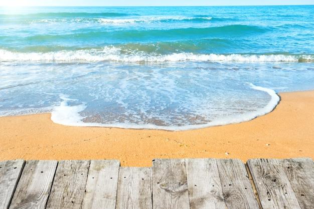 背景に砂と海の波と夏の熱帯のビーチの木製の机からの眺め