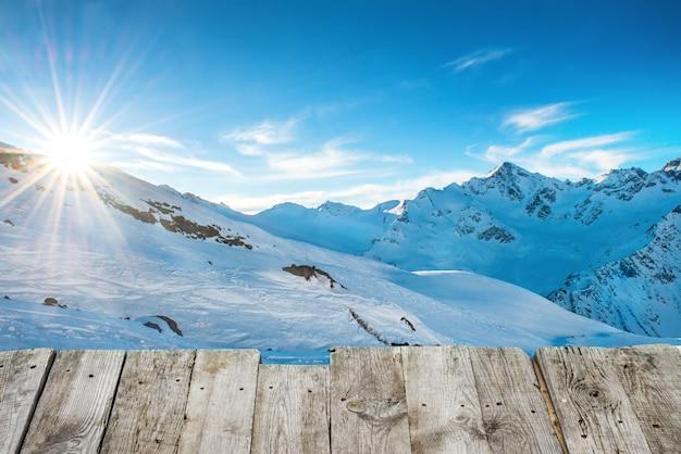 눈으로 덮인 겨울 산에서 나무 테이블에서 일몰까지 볼 수 있습니다. 푸른 하늘에 빛나는 태양과 개념