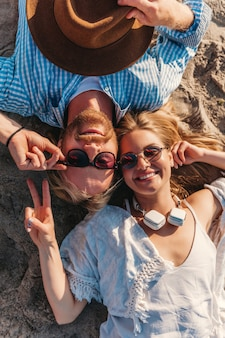 View from above on young attractive smiling happy man and woman in sunglasses lying on sand beach