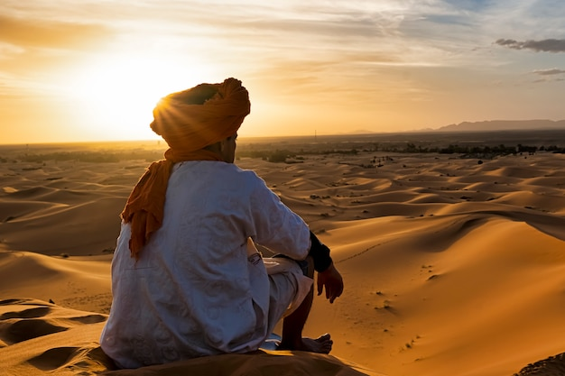 View from behind of a young desert native who watches the dunes of morocco at sunset