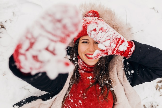 Vista dall'alto sulla giovane donna felice sorridente piuttosto candida in guanti rossi e cappello lavorato a maglia che indossa mantello nero che giace nella neve nel parco, vestiti caldi, divertendosi