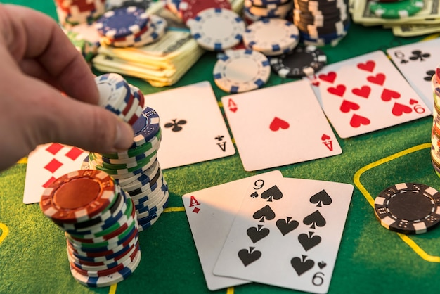 View of a gaming table with many poker card and chips green mat