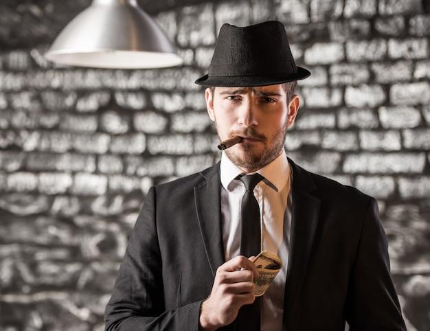 View of a gangster man is smoking a cuban cigar.