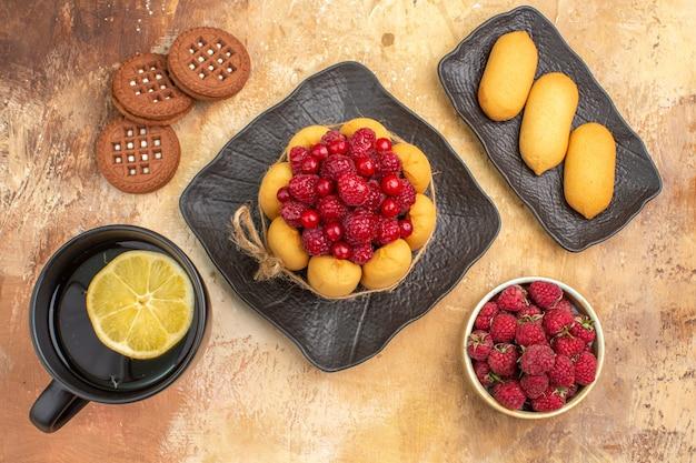 Sopra la vista di una torta regalo e biscotti su piatti marroni su tavola di colori misti