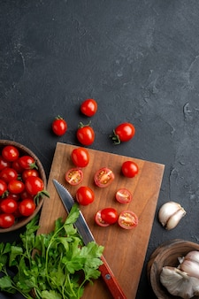 Above view of green bundle fresh tomatoes on wooden cutting board and in bowl on black distressed surface