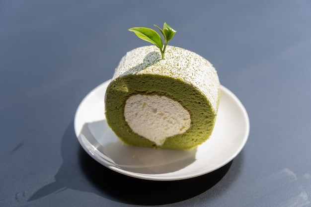 View of green tea cake roll put on top of wooden table.