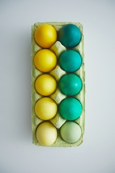 Above view of green and yellow hand painted easter eggs in crate arranged in minimal composition on white background, copy space