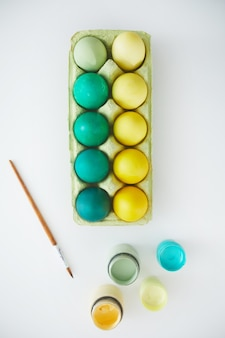 Above view of green and yellow hand painted easter eggs in crate arranged in minimal composition with paint brush on white background, copy space