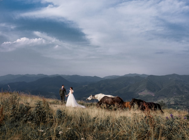 View of groom and bride with the mountain landscape, with horses on the sunny summer day
