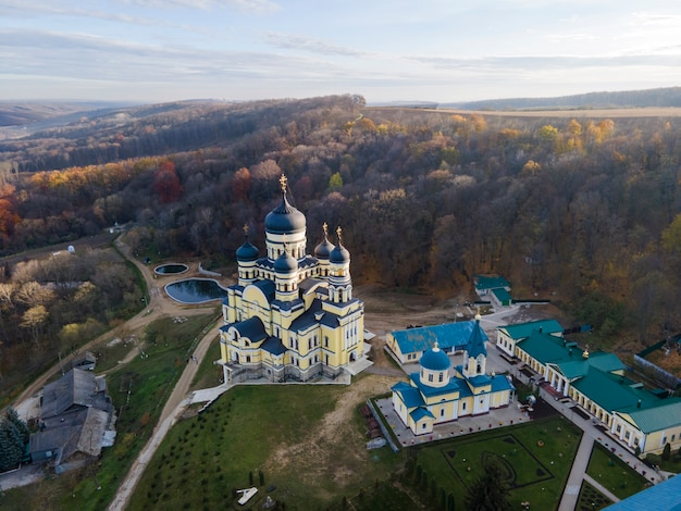 View of the hancu monastery from the drone. churches, other buildings and green lawns. hill with bare trees near it. moldova
