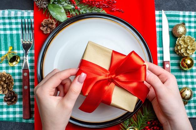 Sopra la vista della mano che tiene una bellissima confezione regalo con nastro rosso a forma di fiocco su un piatto e set di posate accessori per la decorazione su asciugamano spogliato verde