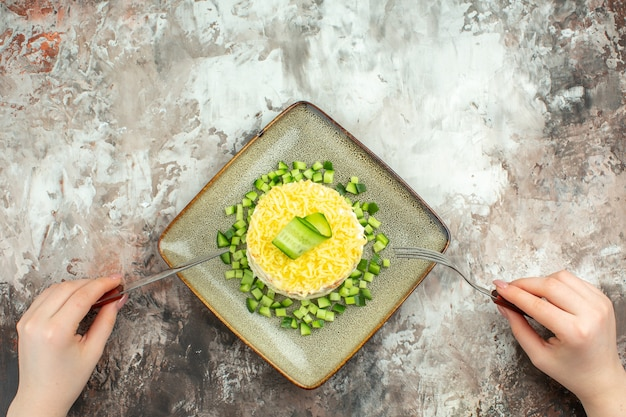 Above view of hand holding fork and knife on tasty salad served with chopped cucumber on mixed color background