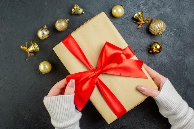 Sopra la vista della mano che tiene una confezione regalo con nastro rosso e accessori di decorazione su sfondo scuro