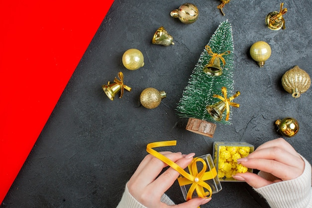 Above view of hand holding gift boxes and christmas tree decoration accessories on dark background