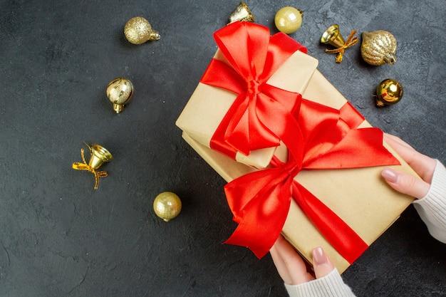 Sopra la vista della mano che tiene una delle scatole regalo con nastro rosso e accessori di decorazione su sfondo scuro