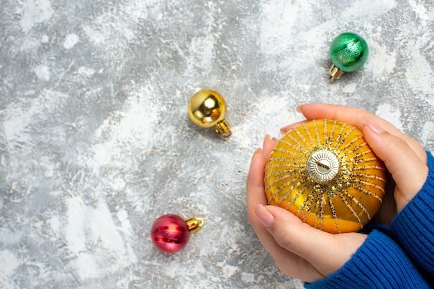 Vista dall'alto della mano che tiene uno degli accessori per la decorazione del nuovo anno sul lato sinistro sulla superficie del ghiaccio