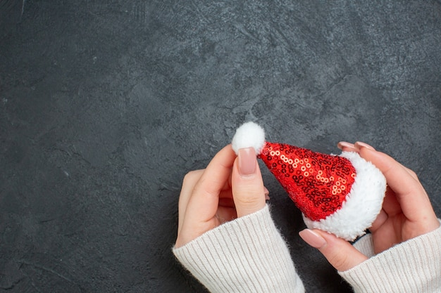 Above view of hand holding santa claus hat on the left side on dark background