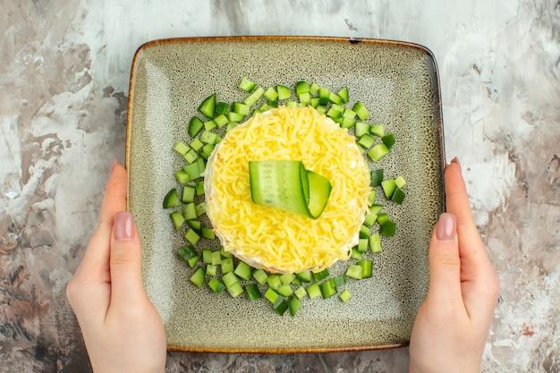 Sopra la vista della mano che tiene una gustosa insalata servita con cetriolo tritato su sfondo di colore misto