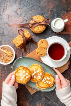 Above view of hand taking tray with fresh pancakes a cup of black tea on a wooden cutting board honey stacked cookies milk on a dark surface