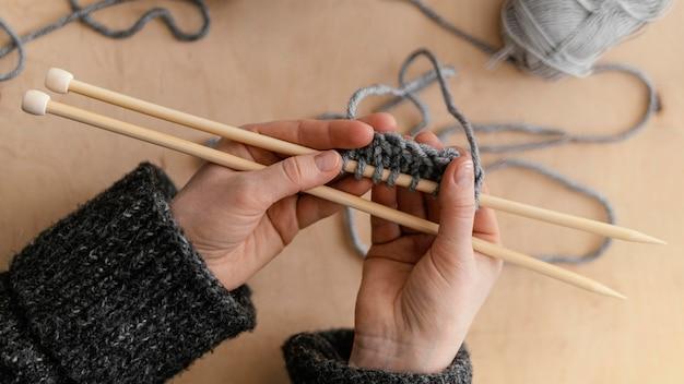 Vista sopra le mani che tengono i ferri da maglia