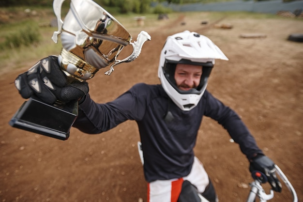 Above view of happy motorcyclist in gloves raising hand with winning cup while showing award for of-road competition