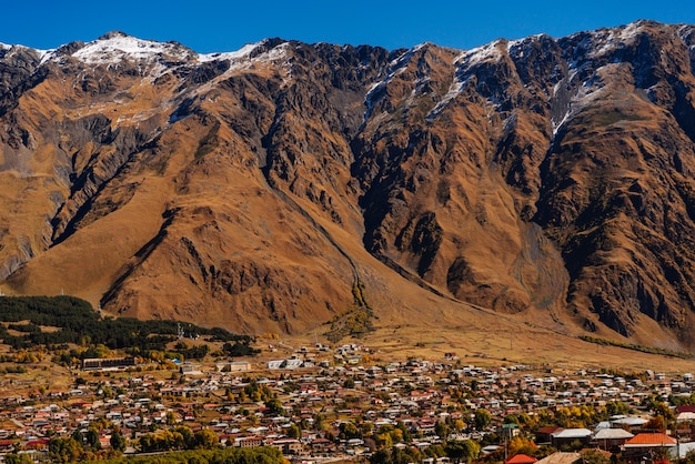 View of the high caucasian snow-capped mountains, a small town, many houses