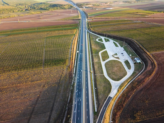 View of a highway with cars from the drone, parking, fields forest in romania