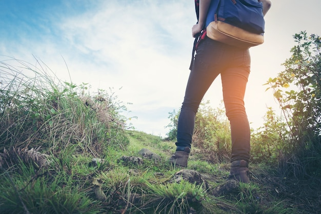 View of hiker legs walking on a path. active woman backpacker traveling on the nature.