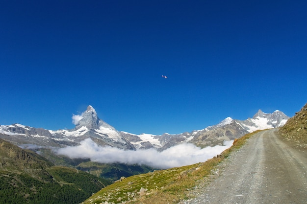 View of hiking trail in swiss alps, zermatt mountains area near matterhorn peak in summer, switzerland