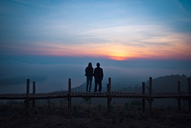 View on hill lover couple silhouette standing on a wooden bridge
