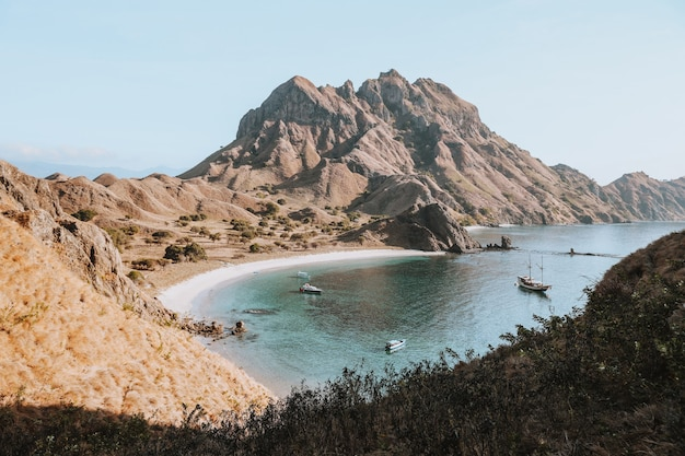 View of the hills and coast and several sailing boats on padar island