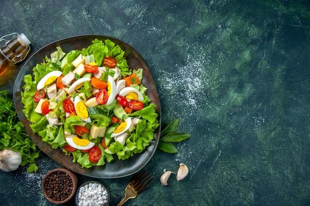 Sopra la vista di una deliziosa insalata fatta in casa con molti ingredienti in un piatto e spezie caduti sulla forcella della bottiglia di olio sul tavolo dei colori della miscela verde nero con spazio libero