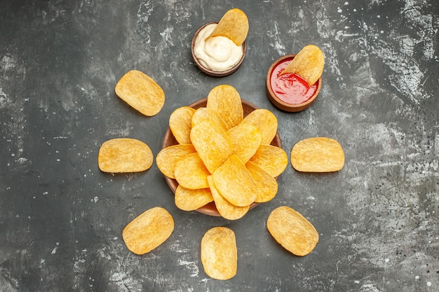 Above view of homemade potato chips arranged in a circle and mayonnaise ketchup on gray table