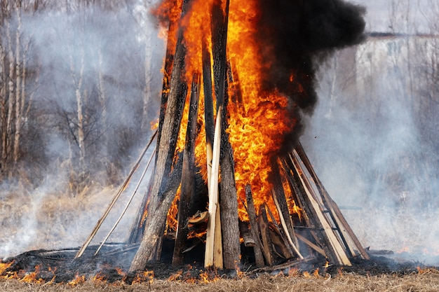 View of huge bonfire of wooden boards and car tires, strong flame of red fire, curling black smoke into sky.