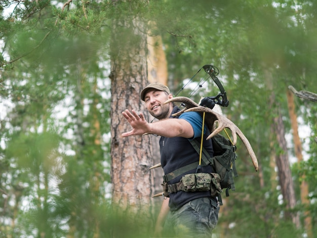 View of a hunter in the woods carries moose horns on his back
